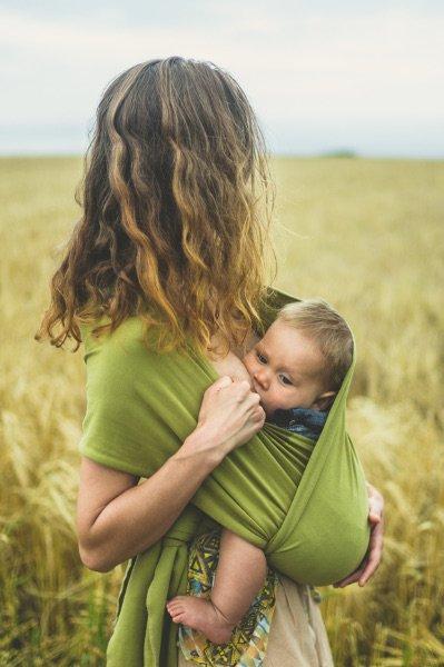 Une maman allaite son bébé en portage dans la campagne
