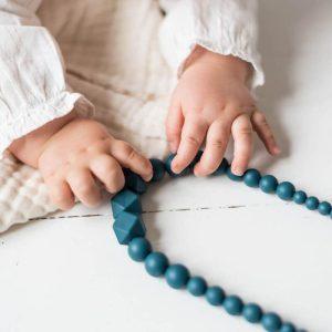 Le collier Peacock de MintyWendy dans les mains d'un bébé