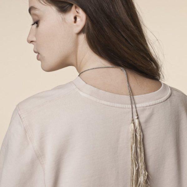 Le bola de grossesse se ferme avec un noeud, laissant pendre les jolies pompons métallisés dans le dos