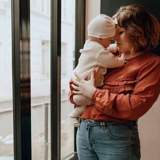 La blouse d'allaitement Bohemilk, coloris terracotta, portée par une maman qui tient son bébé dans les bras