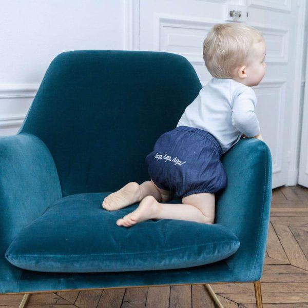 Un bébé habillé du bloomer Joey, sur un fauteuil