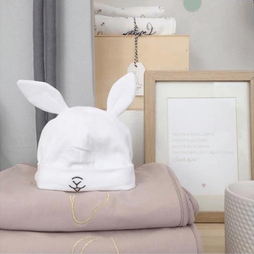 Le bonnet de naissance posé sur des couvertures roses