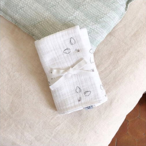 Le maxi lange imprimé museaux plié et posé sur un canapé