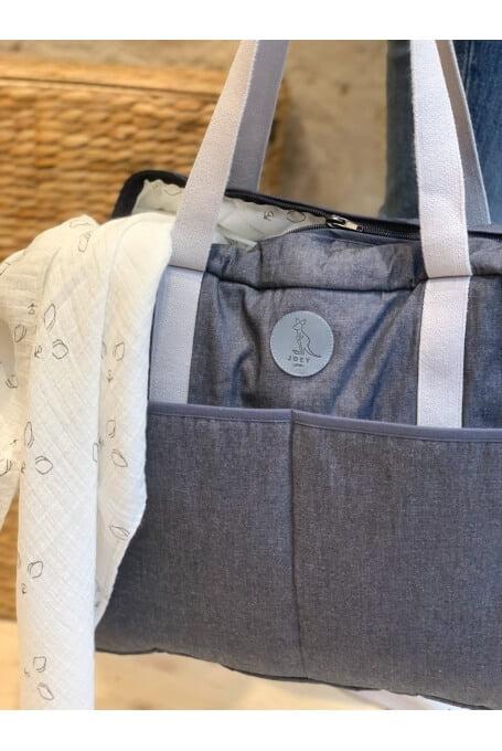 Petit détail en cuir avec le logo de la marque sur le sac à langer Joey