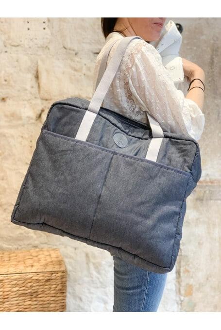 Une maman porte le sac à langer à l'épaule