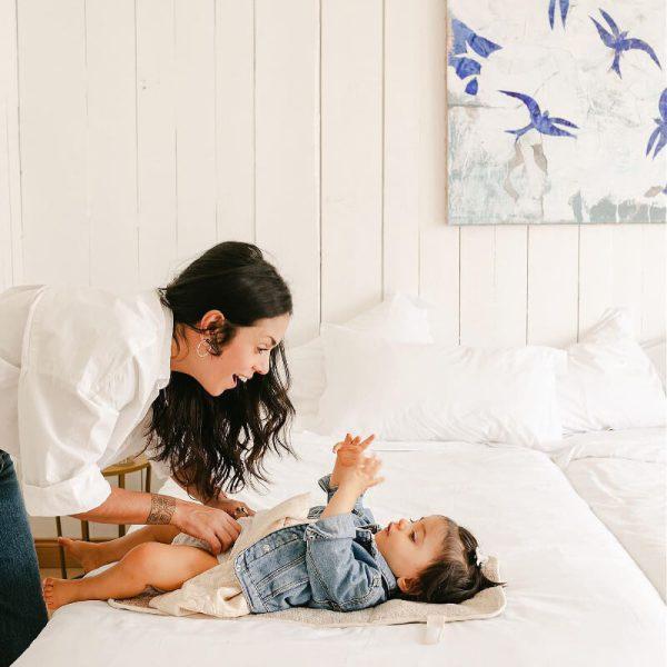 Une maman utilise le matelas à langer Adorna pour changer sa fille